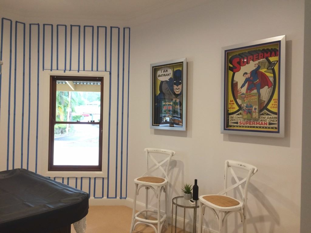 pool room taped up before painting and batman and superman framed comics