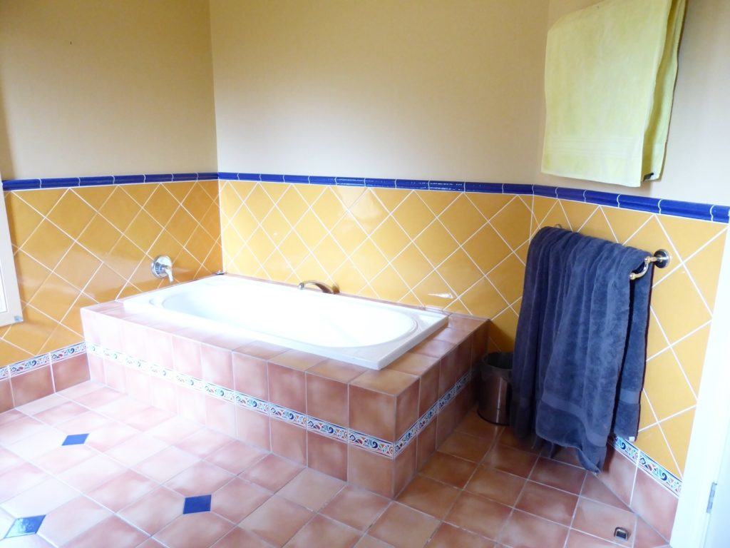 Original kids bathroom before renovation bathtub with floor and wall tiles