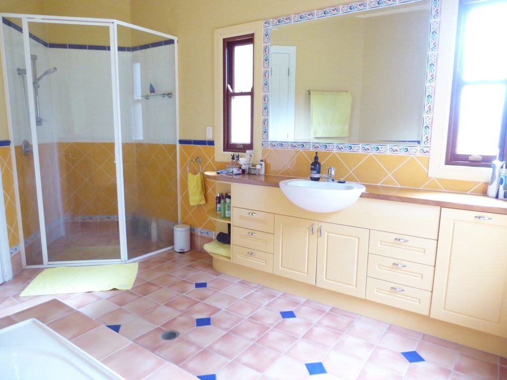Original kids bathroom before renovation cabinetry, shower and tiles