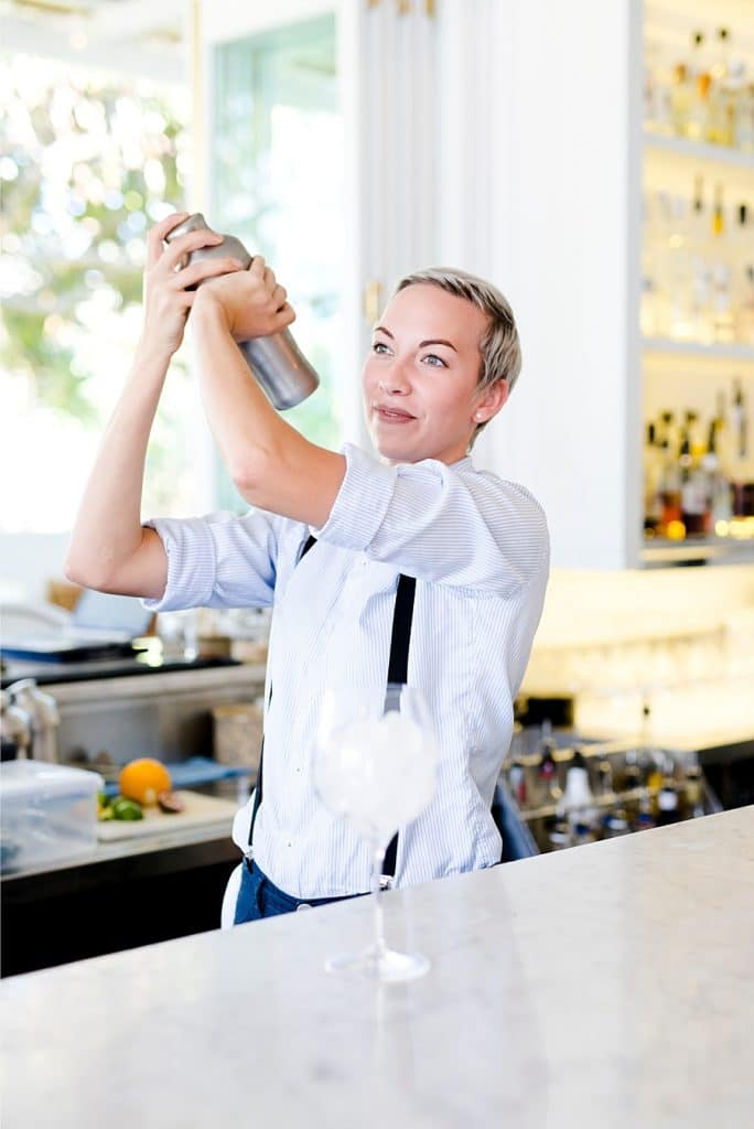 A bartender making the halcyon house signature cocktail